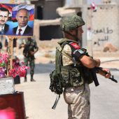 (FILES) In this file photograph taken on August 20, 2018, members of Russian and Syrian forces stand guard near posters of Syrian President Bashar al-Assad and his Russian counterpart Vladimir Putin at the Abu Duhur crossing on the eastern edge of Idlib province. - Russia and Turkey are in intense negotiations to ensure the rebel-held province of Idlib does not become a breaking point in their alliance on Syria, but the long term fate of the area still risks provoking a rupture, analysts say. President Vladimir Putin and Turkish counterpart Recep Tayyip Erdogan have spearheaded an unlikely but so far sustained partnership to bring peace to Syria since late 2016, despite being in theory on opposite sides of the civil war.The cooperation now faces its biggest test over Syria's northwestern province of Idlib, bordering Turkey, which Syrian President Bashar al-Assad wants to recapture to complete a string of military successes. (Photo by George OURFALIAN / AFP)GEORGE OURFALIAN/AFP/Getty Images